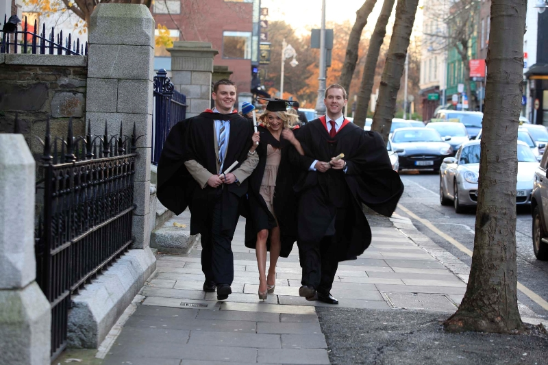 Three happy business graduates on road side