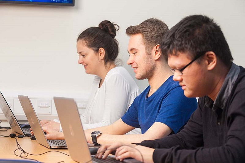 three business student working with laptop