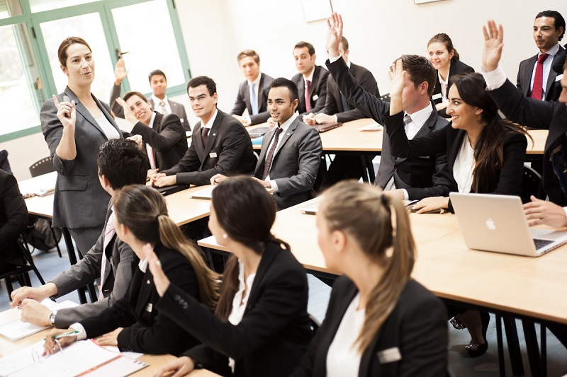 Portrait of business people in business school raising hands in training session